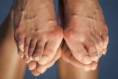Füße mit dem großen Knochen auf dem Spielzeug, das im Spiegel sich reflektiert Stockfotos