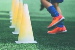 Füße mit den Fußballstiefeln, die auf Ausbildungskegel auf Fußballboden ausbilden lizenzfreie stockfotografie