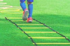 Füße mit den Fußballstiefeln, die auf Beweglichkeitsgeschwindigkeitsleiter im Fußballtraining ausbilden stockfoto