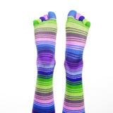 Füße mit gestreiften Socken Stockfoto