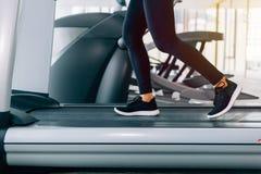 Füße mit Turnschuhen des weiblichen Läufers/des Rüttlers, die zuhause auf Tretmühle in Aktion - mit Bewegungsunschärfe laufen lizenzfreie stockfotografie