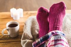 Füße oben in den gemütlichen wolligen rosa Socken mit Tasse Tee und Kerzen Stockbilder