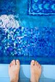 Füße am Rand des Pools Stockfotos