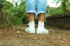 Füße und Beine der jungen Frau in der zufälligen Kleidung stockfotografie