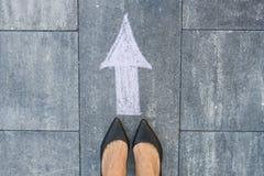 Füße und Pfeil auf Straße Stockbild