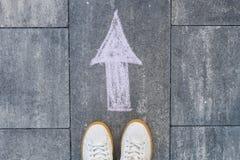Füße und Pfeil auf Straße Lizenzfreie Stockfotografie