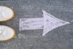 Füße und Pfeil auf Straße Stockfotos