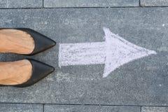 Füße und Pfeil auf Straße Lizenzfreie Stockbilder