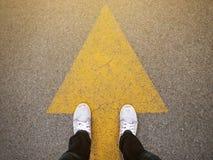 Füße und Pfeile auf Straße Füße und Pfeile auf Straße Lizenzfreie Stockfotos