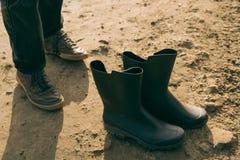 Füße und saubere Stiefel am schlammigen Boden lizenzfreies stockfoto