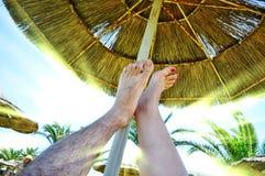 Füße unter dem Regenschirm Lizenzfreies Stockfoto