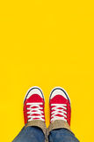 Füße von oben, Jugendlicher in den Turnschuhen, die auf gelbem Backgro stehen stockbild