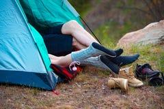 Füße von zwei Leuten, die in einem Zelt liegen Kampieren, Reise, Tourismus, Wanderung und Leutekonzept lizenzfreies stockbild