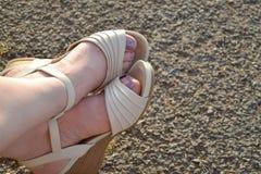 Füße weiße Sandale-auf Kieseln Stockbilder