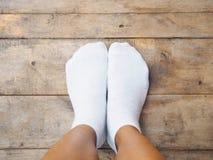 Füße weiße Socken auf Holz tragend lizenzfreies stockbild
