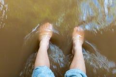 Füße werden im Fluss getränkt Stockfoto