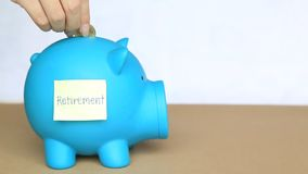 Fügen Sie Münzen in blaues Sparschwein mit klebriger Anmerkung und Ruhestandswort auf Konzept des Einsparungsgeldes für Ruhestand stock footage