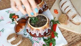 Fügen Sie Pfeffer der Suppe in einem Topf auf einer russischen Feiertagstabelle hinzu stock video