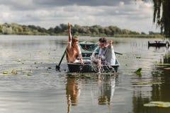 Fühlen spielerisch Schöne junge Paare, die romantisches Datum beim Rudern eines Bootes genießen Glücklich, sich zu haben lizenzfreie stockfotografie
