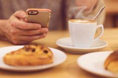 Führen Sie Bild des trinkenden Kaffees und des Haltens des unrecognisable Mannes des intelligenten Telefons beim Frühstücken im R Lizenzfreies Stockfoto