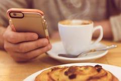 Führen Sie Bild des trinkenden Kaffees und des Haltens des unrecognisable Mannes des intelligenten Telefons beim Frühstücken im R Lizenzfreies Stockbild