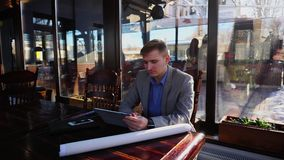 Führen Sie das Grasen mit Tablette und das Sitzen am Café mit Smartphone- und Rollenprojekt auf Tabelle aus n stock video footage