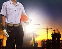 Führen Sie den Mann aus, der mit weißem Schutzhelm gegen Kran und Hochbaustandortgebrauch für Bauingenieur und construc arbeitet Stockbild