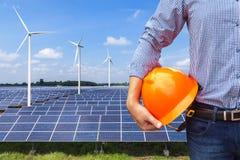 führen Sie den Stand aus, der Solarphoto-voltaisches der gelben Schutzhelmfront halten und die Windkraftanlagen, die StromKraftwe Lizenzfreie Stockfotos