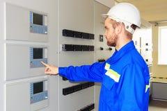 Führen Sie die Technikerelektrogeräte aus, die elektrische Kabinette mit Bedienfeld prüfen Stockfotografie