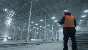 Führen Sie die Unterhaltung am Telefon im neuen modernen Industrielager aus stock footage