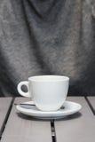 Führen Sie Schuss einer weißen Kaffeetasse auf einem grauen Holztisch einzeln auf Lizenzfreie Stockfotografie