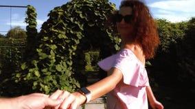 Führender Freund der Frau, der hinunter den Garten geht stock footage