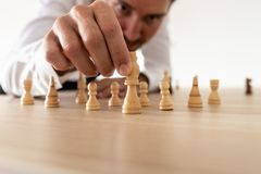 Führender Vertreter der Wirtschaft, der Schachfiguren mit König in der führenden Position vereinbart lizenzfreies stockbild
