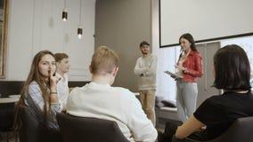 Führer spricht mit Team im Konferenzsaal, Showzeichen des jungen Mädchens der Ruhe stock video