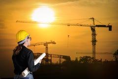 Führt Frau an der Baustelle auf Hintergrund aus Lizenzfreie Stockfotos