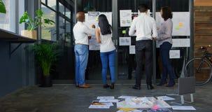 Führungskräfte, die über Architekturmodell und klebriger Anmerkung 4k sich besprechen stock footage
