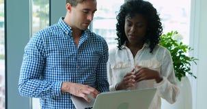 Führungskräfte, die über Laptop im Büro sich besprechen stock footage