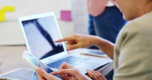 Führungskräfte, die über Laptop und Handy sich besprechen stock video