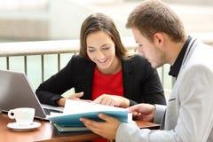 Führungskräfte, die Dokumente in einer Kaffeestube konsultieren lizenzfreie stockbilder