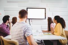 Führungskräfte, die am Fernsehen während des Trainings im kreativen Büro aufpassen lizenzfreies stockfoto