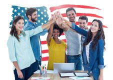 Führungskräfte, die Handstapel gegen amerikanische Flagge im Hintergrund im Büro tun Lizenzfreie Stockbilder
