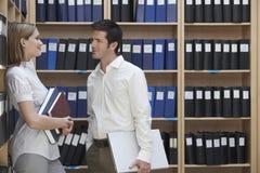 Führungskräfte, die im Aktenspeicherungs-Raum sprechen Lizenzfreies Stockbild