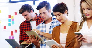 Führungskräfte, die Laptop, Handy, digitale Tablette im Büro verwenden stock video footage