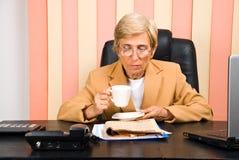 Führungskraftlesenachrichten und trinkender Kaffee Lizenzfreie Stockfotos