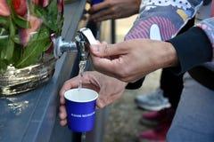 Füllen eines Glases Wassers vom Hahn Stockbilder
