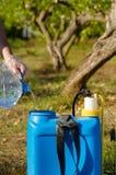 Füllen eines Schädlingsbekämpfungsmittelsprühers lizenzfreies stockfoto