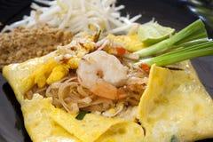 Füllen Sie die thailändischen, gebratenen Nudeln mit Garnelen im Omelett auf lizenzfreies stockfoto