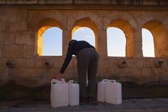 Füllende Dosen des Mannes mit Brunnenwasser Stockbild