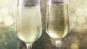 Füllende Flöten des Champagners mit goldenen Blasen gegen Gold-bokeh Hintergrund, Konzept des goldenen Luxusfeiertagsguten rutsch stock video