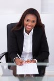 Füllende Form der überzeugten Geschäftsfrau am Schreibtisch im Büro Stockbilder